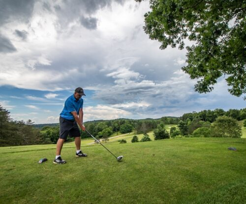 Man teeing off on golf course