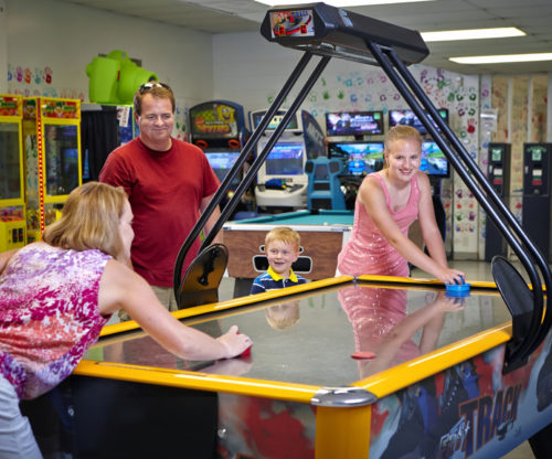 Family Playing In Game Room