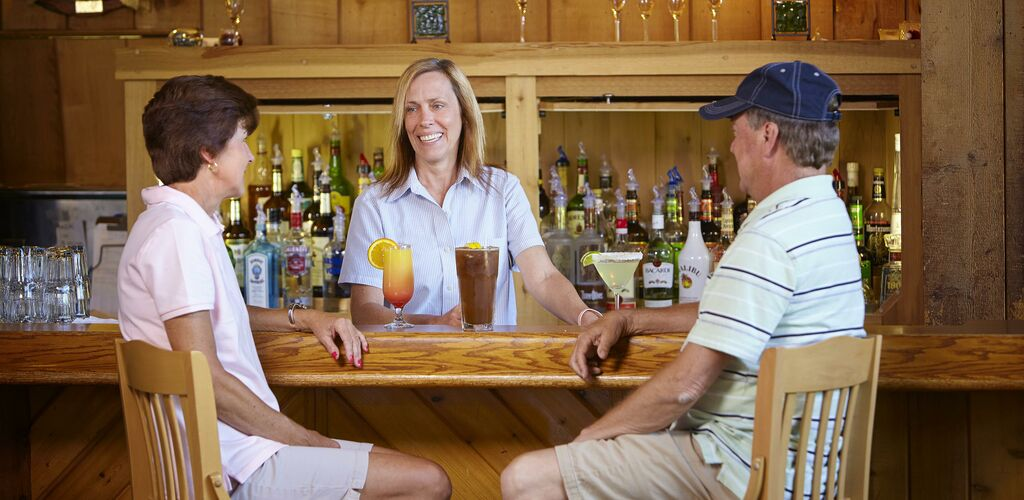 Bar with bartender and a couple ordering drinks